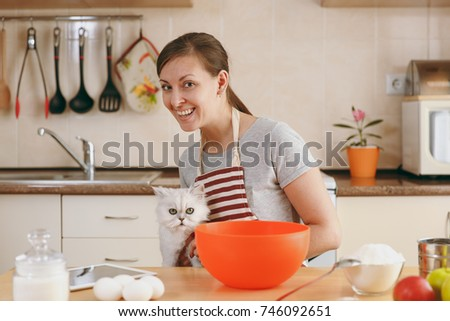 The young beautiful happy woman with a white Persian cat prepares dough for Christmas cakes with tablet on table in the kitchen. Cooking home. Prepare food. #746092651
