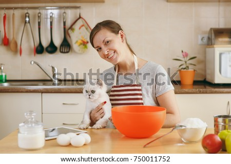 The young beautiful happy woman with a white Persian cat prepares dough for Christmas cakes with tablet on table in the kitchen. Cooking home. Prepare food. #750011752