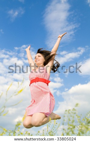 The young beautiful woman in a jump, hands are lifted upwards, on a background of the blue sky, smiles