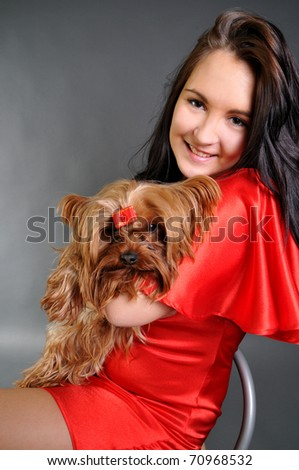 The young beautiful woman in a red dress with the terrier - stock photo