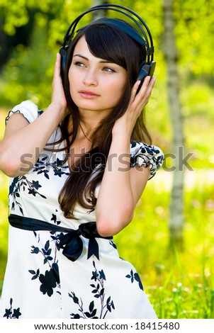 The young beautiful woman listens to music through ear-phones against a birch-wood.