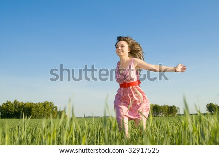 The young beautiful woman quickly runs on a glade, smiles, hands are opened
