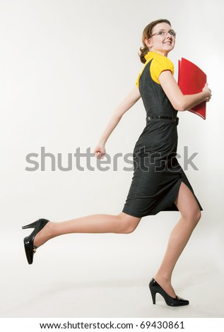 The young beautiful woman runs with a red folder in hands