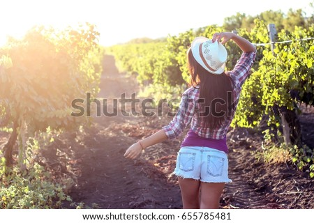 The young beautiful woman walks in the vineyards. Portrait of a beautiful young woman with a hat in summer rays of the sunset. Happy young woman enjoying summer sunset in the vineyard.