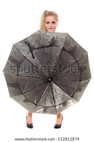 The young blonde looks out from for a umbrella
