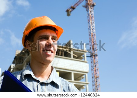The young builder inspector on a background of building object.