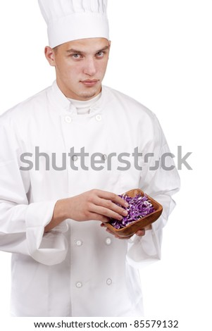The young chef in uniform and chef's hat in his hands chopped red cabbage.