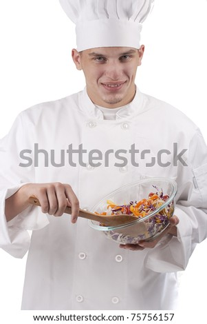 The young chef in uniform and chef's hat in the bowl of salad mixes.