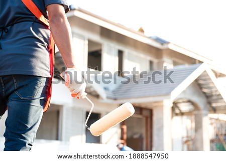 The young construction contractor plans to paint a big house. ストックフォト ©