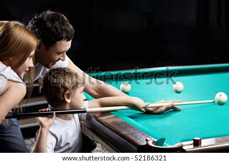 The young couple and the child plays billiards
