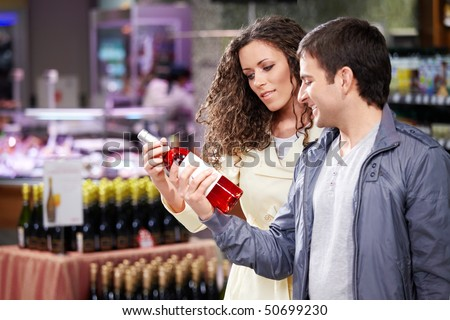 The young couple chooses a wine bottle in shop