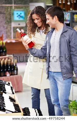 The young couple chooses wine in shop