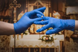 The young couple puts on wedding rings wearing protective gloves. Marriage during a coronavirus epidemic. Covid-19