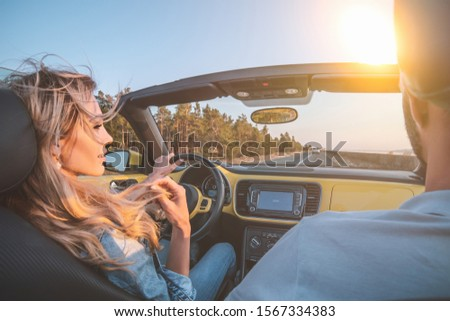 The young couple traveling by a cabriolet
