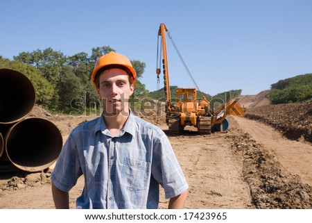 The young engineer on a working platform on stacking a new oil pipeline.