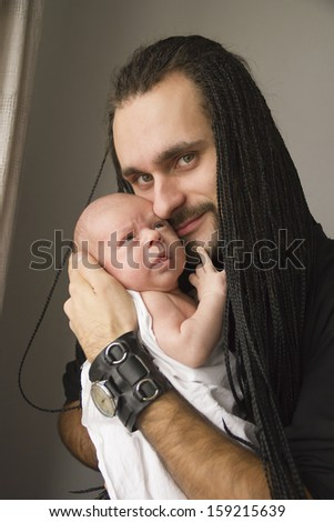 the young father with the baby on hands on a gray background