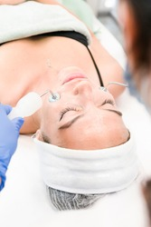 The young female client of cosmetic salon having microcurrent procedure on her face with special devices, close-up. Beautician using electrical impulses for facial procedures. Concepts of skin care