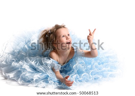 The young fine girl (child) in a blue dress sits on a white background