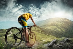The young fit man in helmet conquering mountains on a bicycle. The bike, nature, bicycle, sport, cycle, extreme, lifestyle, adventure and sport concept