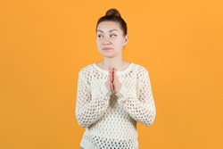 The young girl cunningly looks away, rubbing her hands. Isolated on a yellow background