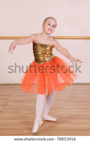 The young girl dances in a ballet orange tutu in the hall