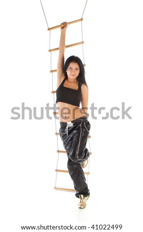 The young girl hangs on a rope ladder