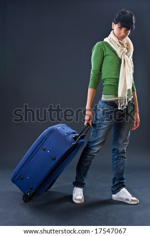 The young girl in a scarf and jeans with a dark blue suitcase on a dark background