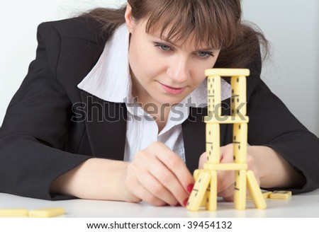The young girl in black concentrated builds on a table a tower of dominoes