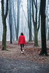 The young girl in the red sweater is walking alone in the cold foggy forest