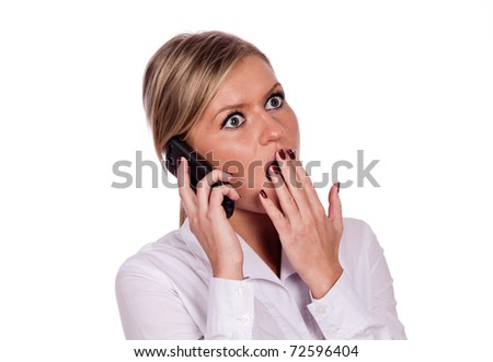 The young girl is holding a cell phone  with a surprised expression