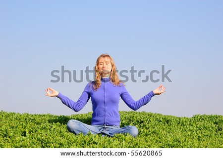 The young girl meditates in a spring field