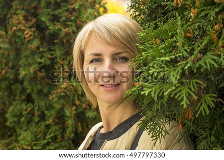 The young girl near green tree branches. Image of a girl clear. The rest is blurry. There are a model release. - Shutterstock ID 497797330