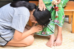 The young girl prostrated grandmother's feet to show love and gratitude.