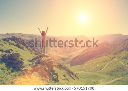 The young girl raised her arms up to the sun on a background of mountains