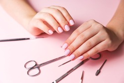 The young girl's hands are well-groomed, her nails are manicured. Manicure tools are spread out on the table. The girl did her own manicure during the quarantine, when it was impossible to leave the