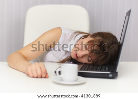 The young girl sleeps having placed a head on the laptop keyboard