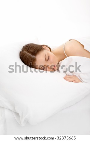 The young girl sleeps in the white bed, isolated