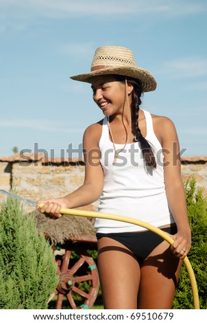 The young girl the farmer watering from a hose