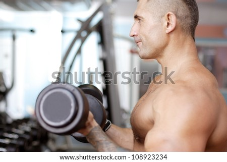 the young guy lifts an apparatus against a gym
