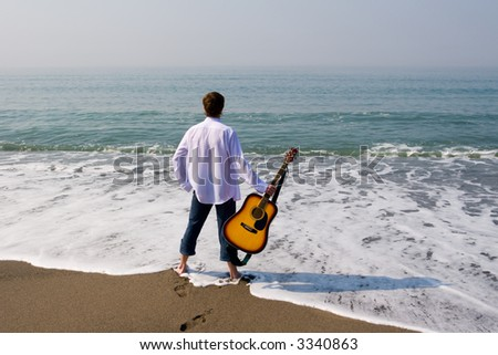 The young guy (musician) walks on a beach with a guitar.