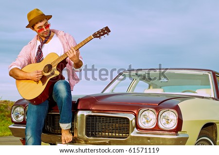 The young guy plays on a guitar sitting on a cowl of the old car