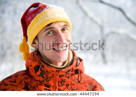 The young guy smiles against winter wood