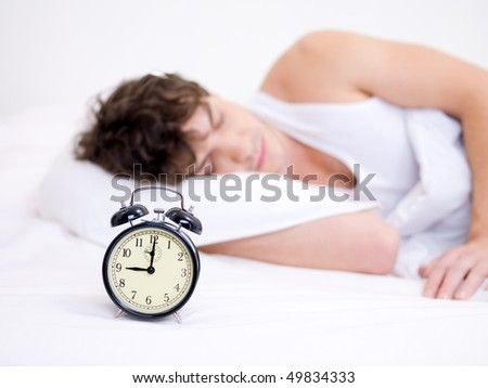 The young handsome man sleeping with alarm clock near his head