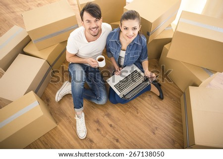 The young happy couple searching for apartments with laptop. Moving, purchase of new habitation.
