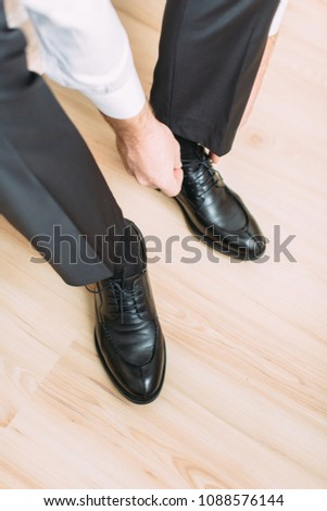 The young happy groom wears black shoes for the wedding #1088576144