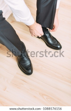 The young happy groom wears black shoes for the wedding #1088576156