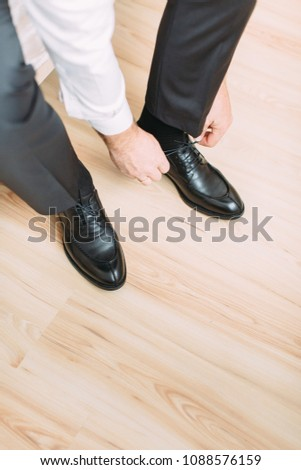 The young happy groom wears black shoes for the wedding #1088576159