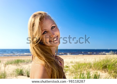 The young happy woman on a beach.