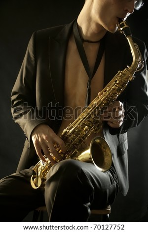 The young jazz man plaing a saxophone on black