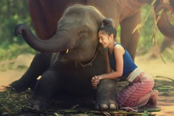 The young lady is sitting together with her best friend elephant.